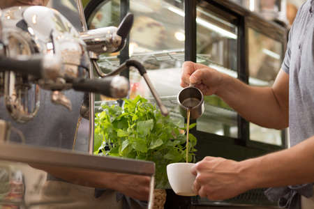 cropped shot: Cropped shot of a male barista preparing a coffee Stock Photo
