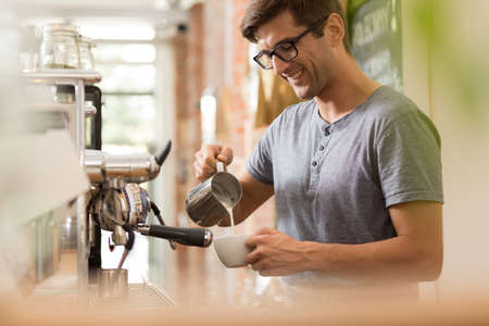 cropped shot: Cropped shot of a smiling barista adding milk to the coffee