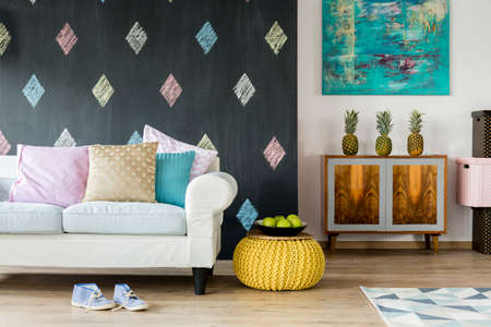 commode: Modern interior with blackboard, white sofa with pastel cushions and exotic commode