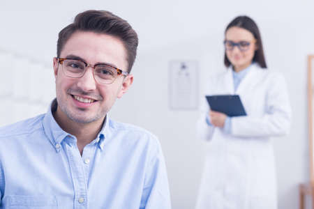 Happy handsome young man wearing stylish glasses with thin brown frames. In the background young optician