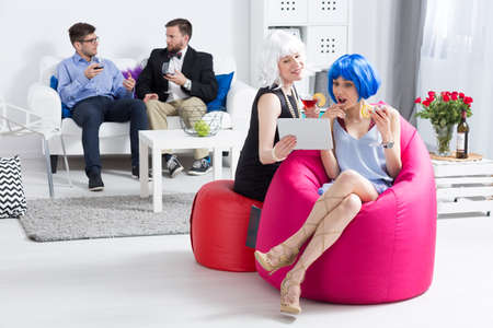 wigs: Two young women in colourful wigs having drinks and sitting on sit sacks at a party in a modern flat, with their friends in the background