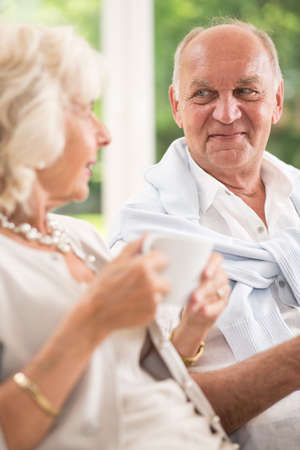 couple on couch: Elderly couple sitting on couch and relaxing with tea Stock Photo