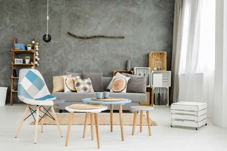 Image of a new style grey flat with DIY furniture, sofa, small table and chairs