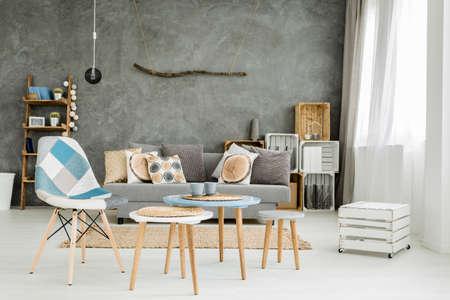 Imagen de un nuevo estilo plano gris con muebles de bricolaje, sofá, mesa y sillas
