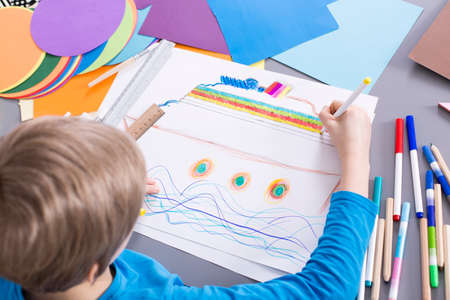 Creative young boy painting colorful boat on a white paper during art classes at school