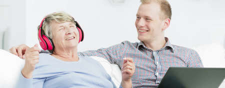 clarify: Close shot of elder woman with pink earphones and closed eyes and young man, sitting together in front of the laptop screen Stock Photo