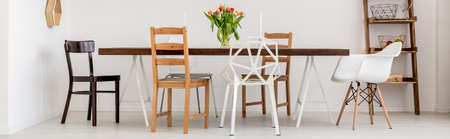 lightsome: White dining room with wooden table and design chairs Stock Photo