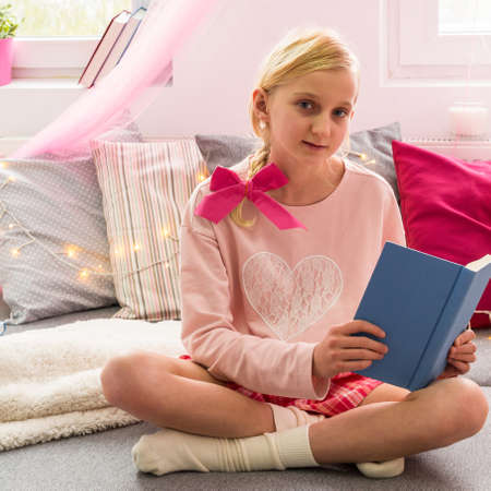 cross legged: Girl with book sitting on the bed