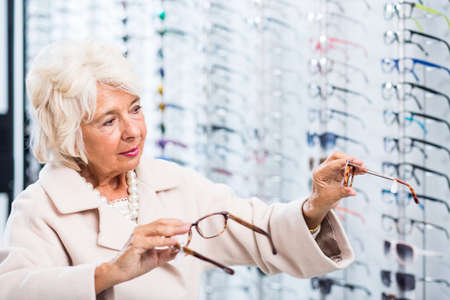 dudando: Hesitating elderly woman choosing from a wide variety of glasses at the opticians Foto de archivo