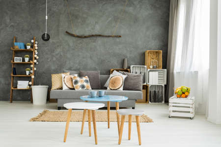 Spacious living room in new style with sofa, small table, two chairs and DIY cabinet Archivio Fotografico
