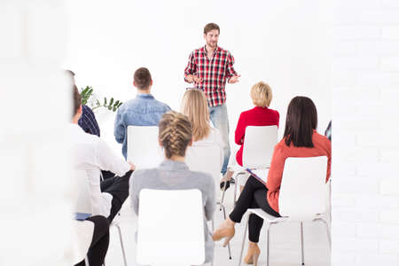 business people meeting: Young confident happy man discussing with his corporate team about new ideas for success