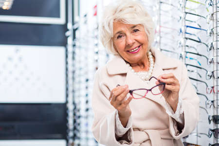 optician: Elegant senior lady at the opticians, trying on one of the many glasses frames