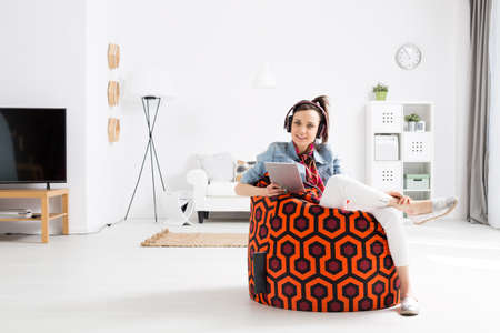Smiling female student listening to music on a sit sack inside a very bright living room Stock Photo