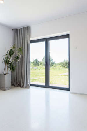 Shot of a minimalistic apartment interior with a large window and white floor