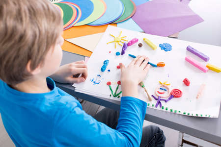 Young creative boy having art classes at school. Doing a picture from colorful plasticine Stock Photo