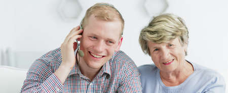 earpiece: Close shot of an older woman and a man with an ear-piece with microphone sitting together and smiling Stock Photo