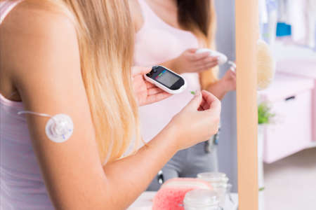 hyperglycemia: Young sick girl with insulin pump injection on arm Stock Photo