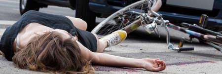 lesionado: ciclista femenino inconsciente tirado en la calle después del accidente de tráfico