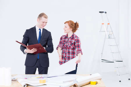 refurbishment: Shot of a young interior decorator showing her designs to a young businessman