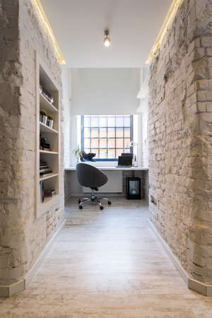 Study Desk: Home office with stylish exposed brick walls, comfortable chair and simple desk