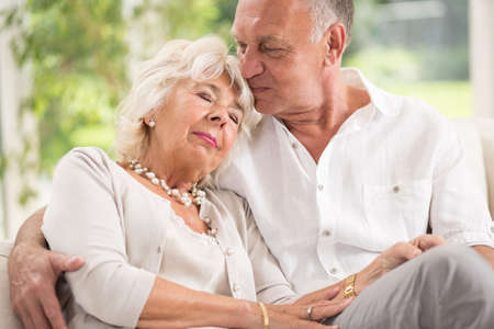 tenderly: Elderly marriage sitting on sofa and hugging tenderly Stock Photo