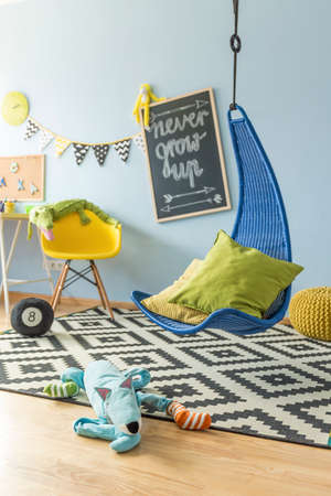 children play area: Shot of a colorful childrens room with a hanging chair  Stock Photo