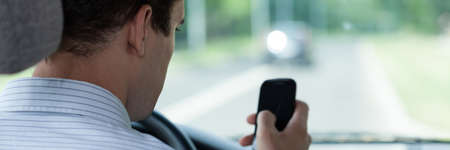 driving a car: Male driver using mobile phone in car, horizontal