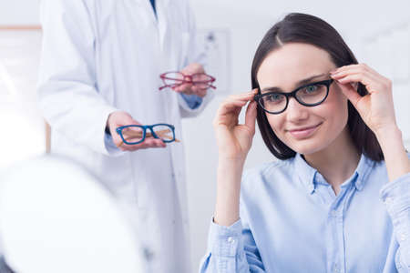 specs: Beautiful young woman choosing new pair of spectacles in opticians store