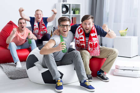 Vier schreeuwen voetbalfans ondersteuning van hun team in een lichte, moderne ruimte, zittend op zitzakken Stockfoto