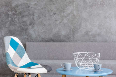 Closeup shot of a blue coffee table and a stylish multicolor chair standing on a gray background Stock Photo