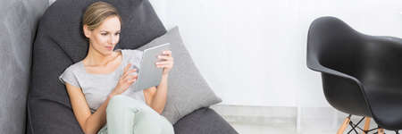 bean bag: Woman sitting on bean bag chair with tablet