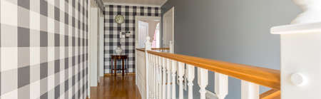 upstairs: Stylish hall on the floor of a house, with checked wallpaper and wooden banister Stock Photo