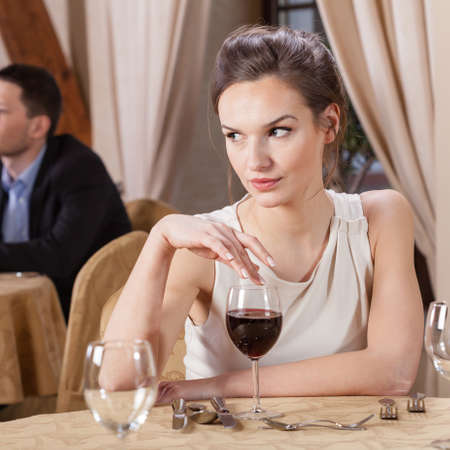 elegant party: Single woman drinking wine in a restaurant