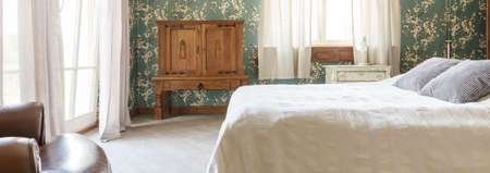 bedroom furniture: Spacious bedroom with decorative pattern wallpaper and solid wooden furniture