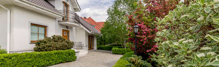 vast: Panoramic photo of an elegant detached house with cobbled front yard and a vast well-groomed garden Stock Photo