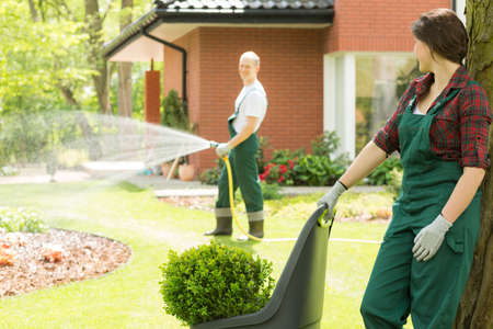 one female: Male gardener watering the garden while the female one is leaning against the tree