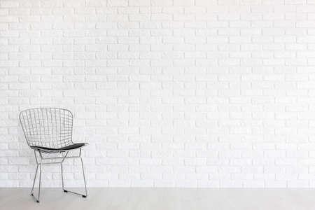 Colpo di una sedia moderna gap contro un muro di mattoni
