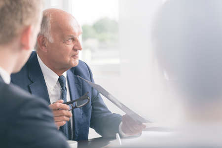 cropped shot: Cropped shot of an elegant senior boss at the meeting with his business partners