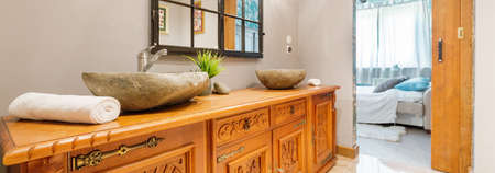 commode: Bathroom with antique wooden commode and stone sink Stock Photo
