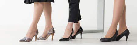 dress code: Close shot of three womans legs in high-heeled shoes each