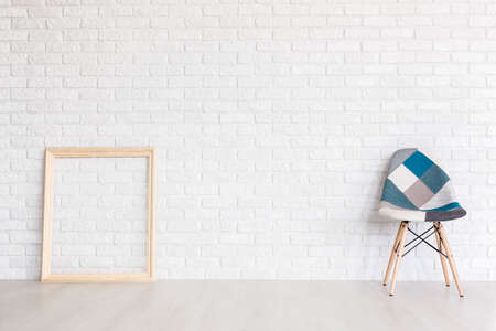 Shot of a wooden frame and a patchwork chair against a white brick wall
