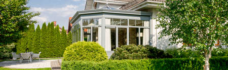 Spacious orangery in a large villa surrounded by a vast garden with hedge and well-groomed trees and grass