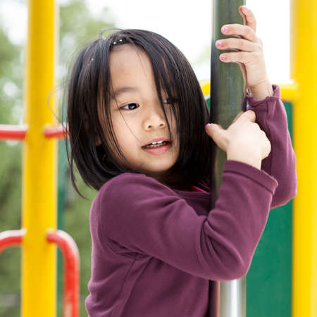 playground: Little asian lady on a playground, vertical