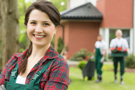 boiler suit: Female gardener in the close-up with two colleagues in the background Stock Photo