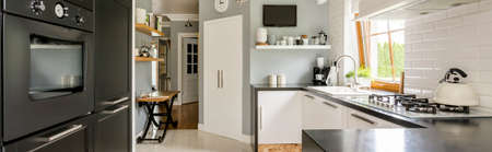 Panorama of contemporary kitchen interior with white cabinets, pantry, built in oven and a large window Reklamní fotografie