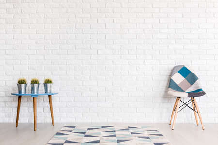 Shot van een moderne kamer met een lappendeken stoel en een tafel met cactussen Stockfoto