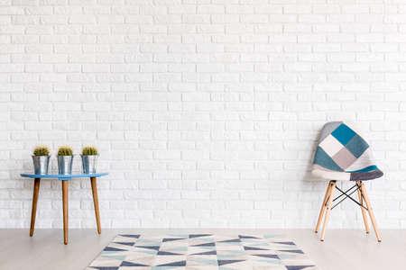 Shot von einem modernen Zimmer mit einem Patchwork-Stuhl und einem Tisch mit cactuses