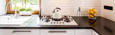 Fragment einer modernen Küche mit einem Waschbecken durch das Fenster, einem weißen Kochfeld und einem Designer-Zitronenpresse