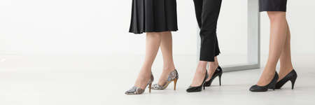 black lady: Close shot of three womans legs in high-heeled shoes each