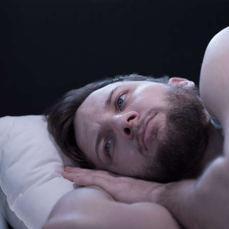 trying: Close-up of young wake up man trying to fall asleep Stock Photo